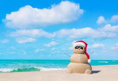 Sandy Snowman in Christmas Santa hat and sunglasses at beach royalty free stock image