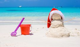 Sandy snowman with red Santa Hat and beach toys royalty free stock image
