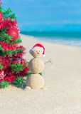 Sandy Snowman in Sankt-Hut unter verziertem Weihnachtsbaum am Strand Stockfotografie