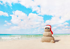 Sandy snowman in santa hat on sea beach. New Years and Christmas stock image