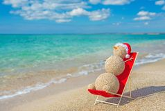 Sandy snowman in santa hat sunbathing in beach lounge. Royalty Free Stock Photo