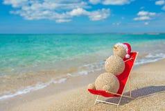 Sandy snowman in santa hat sunbathing in beach lounge. royalty free stock photo