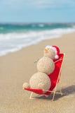 Sandy snowman in santa hat sunbathing in beach lounge. stock image