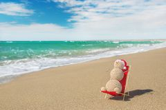 Sandy snowman in santa hat sunbathing in beach lounge. Royalty Free Stock Photography
