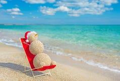 Sandy snowman in santa hat sunbathing in beach lounge. stock photo