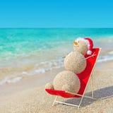 Sandy snowman in santa hat sunbathing in beach lounge. royalty free stock photography
