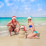 Sandy snowman in santa hat and young happy couple at beach Stock Photos