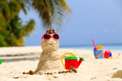 Sandy snowman and toys at sand beach Stock Images