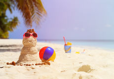 Sandy snowman and toys at sand beach Royalty Free Stock Photo