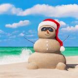 Sandy Snowman in Weihnachts-Sankt-Hut und -Sonnenbrille an tropischem Lizenzfreie Stockbilder