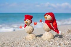 Sandy Snowmen en la playa Años Nuevos de día de fiesta adentro Imagen de archivo
