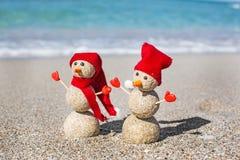 Sandy Snowmen en la playa Años Nuevos de día de fiesta adentro Foto de archivo