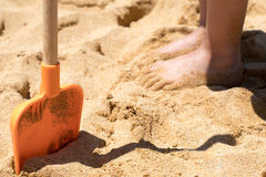 Sandy Spade- und Kinderfüße auf Strand Lizenzfreie Stockfotos