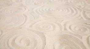 Sandy spirals background. Spirals drawn in white sand Stock Photography