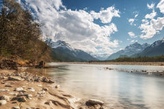 Sandy and stony river bank and blue sky Royalty Free Stock Image