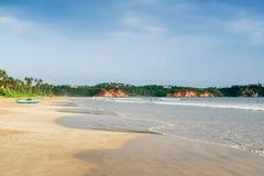 Sandy-Strand, grüner Dschungel, Palmen, Fischerboot auf dem Sand, schwimmende Leute Stockfotografie