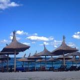 Sandy-Strand mit Eilregenschirmen Lizenzfreie Stockfotos