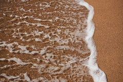 Sandy-Strand mit einem Wellenaufkommen Stockbilder
