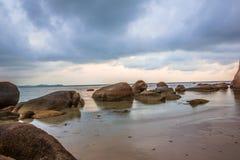Sandy-Strand mit großen Steinen ein späten Nachmittag Stockfotos