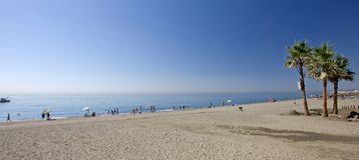 Sandy-Strand mit Palmen in Estepona in Südspanien Lizenzfreies Stockfoto