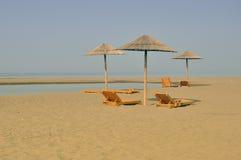 Sandy-Strand mit sunbeds Lizenzfreies Stockfoto