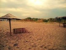 Sandy-Strand, Sonnenschirm und sunbad Stockfotos