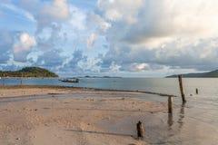 Sandy-Strand und gehendes Fischerboot während des Sonnenuntergangs Lizenzfreie Stockfotos