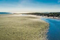 Sandy-Strandansicht mit Pfützen und Felsen Stockbild
