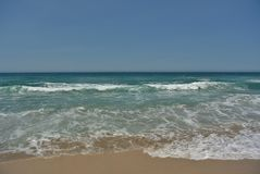 Beach with ocean waves and aqua blue water royalty free stock photography