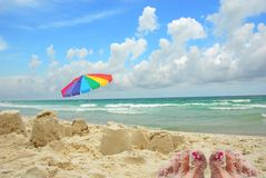 Sandy Toes and Sand Castles. Woman's sandy toes laying next to sandcastles at pretty oceanside setting Royalty Free Stock Image