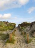 Sandy Trail eller strandpromenad till stranden under blåa molniga himlar Arkivbild