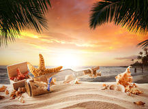 Sandy tropical beach with bottle and starfish Royalty Free Stock Photo