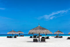 Sandy tropical beach with deckchairs and sunshades. Maldives Stock Photo