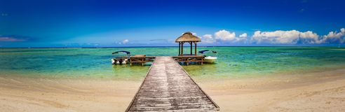 Sandy tropical beach. Jetty on the foreground. Panorama royalty free stock image