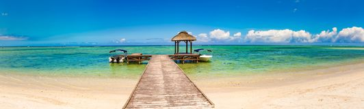 Sandy tropical beach. Jetty on the foreground. Panorama stock photo