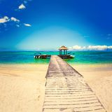 Sandy tropical beach. Jetty on the foreground. royalty free stock image