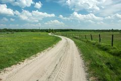 Sandy winding road through green pastures, wooden posts in the fence royalty free stock image