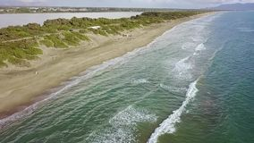 Sandy beach spit washed by the water on both sides. Aerial survey. Slow motion. Sandy yellow beach spit washed by the water on both sides under the grey thick stock footage