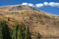 Sandy Yellow Mountain par un lac avec des pins Images stock