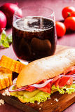 Sandyich με το ζαμπόν και τα λαχανικά και ένα ποτήρι της κόλας σε έναν ξύλινο πίνακα Στοκ Φωτογραφία
