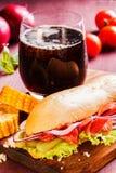 Sandyich con el jamón y verduras y un vidrio de cola en un tablero de madera Fotografía de archivo