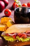 Sandyich con el jamón y verduras y un vidrio de cola en un tablero de madera Foto de archivo libre de regalías