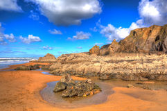 Sandymouth beach North Cornwall England UK beautiful rocks with unusual patterns in colourful HDR Royalty Free Stock Image