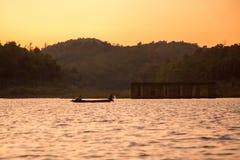 Sangkhlaburi Bridge. A fisherman rides long tail boat across Songkhalia river, Sangkhlaburi, Kanchanaburi, Thailand Royalty Free Stock Photo
