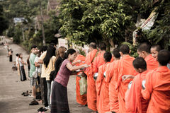Sangkhlaburi morning buddisht. Put food offerings in a Buddhist monk is alms bowl Stock Photos