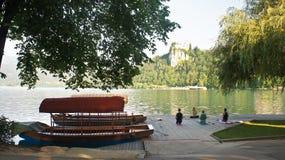 Sangrado, Eslovenia - 07 19 2015: Hermosa vista del lago y castillo, Julian Alps y barcos, mañana soleada, gente que hace yoga imagen de archivo libre de regalías