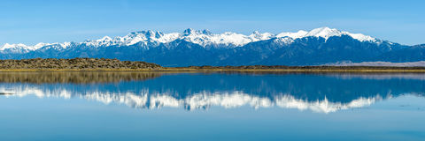 Sangre de Cristo Mountains. Panoramic view of Snow-capped Sangre de Cristo Mountains, reflecting in San Luis Lake. The high peaks in the middle are: Challenger Stock Photography