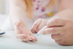 Sangre de medición Sugar Level Of Girl With Glucometer imagen de archivo libre de regalías