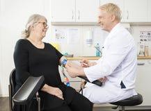 Sangre del doctor Collecting Senior Patient sonriente para la prueba en el Cli fotografía de archivo