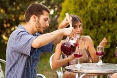 Sangria сервировки Гая с друзьями в террасе Стоковое Изображение